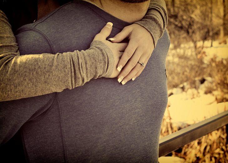 manos de chica abrazando a un hombre