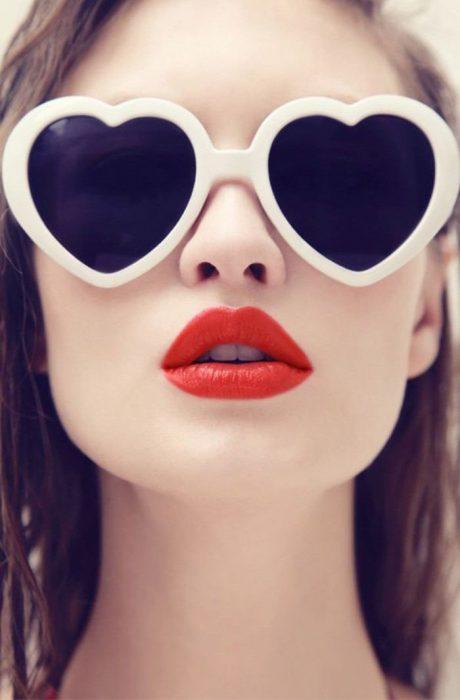 chica con labios rojos y lentes con forma de corazón