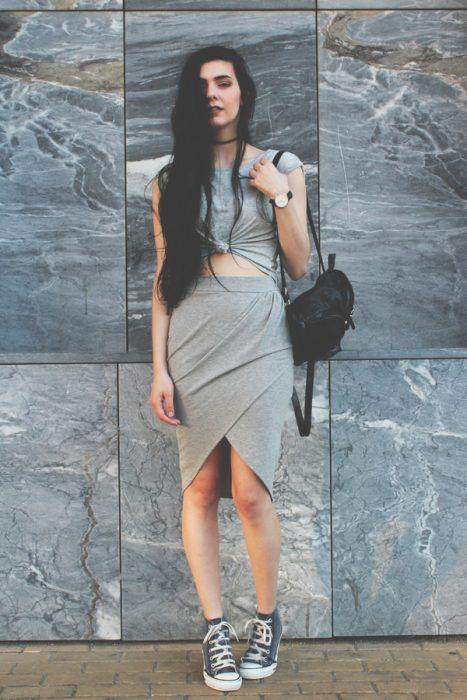 mujer con vestido gris con tenis converse