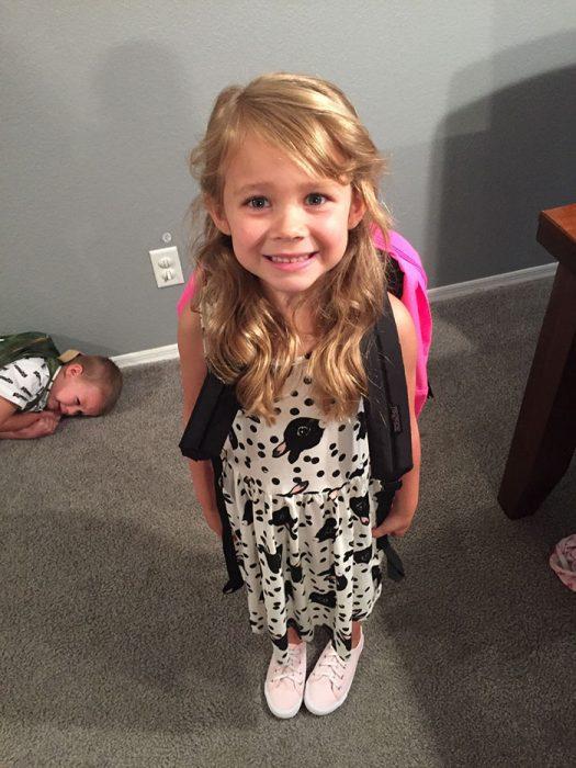 niño en el suelo y niña sonriendo antes de ir a clases