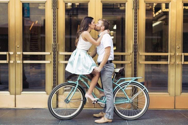 Pareja en bicicleta besándose