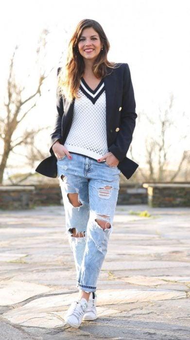 mujer con pantalones rotos y tenis blancos