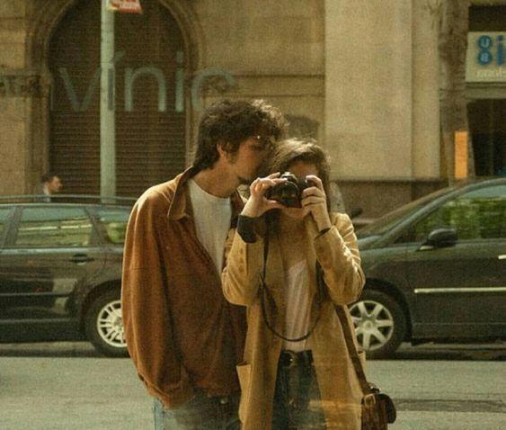 pareja frente aparador tomándose foto con cámara análoga