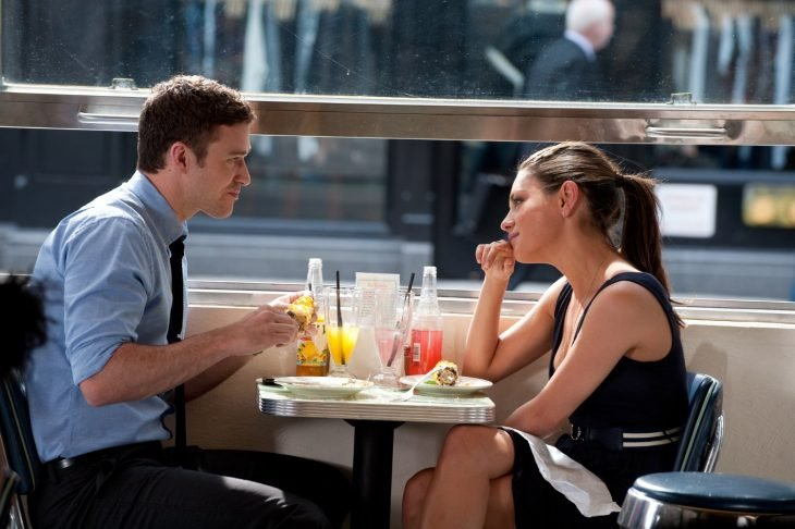 mujer sentada frente a hombre comiendo