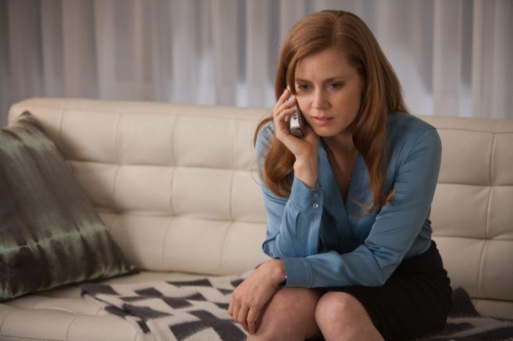 mujer sentada hablando por teléfono