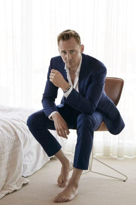 hombre rubio sentado con traje azul sin zapatos