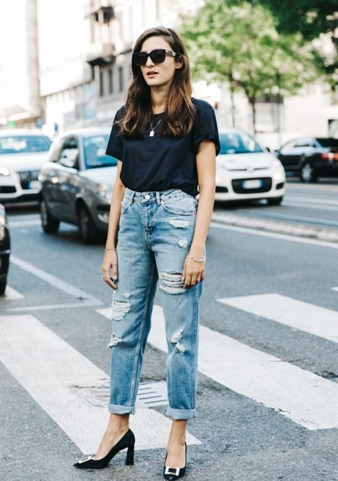 mujer con pantalones rotos y tacones negros