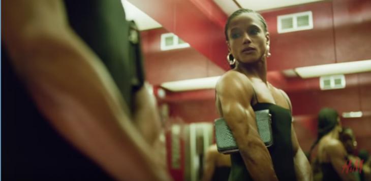 mujer con músculos se mira en el espejo