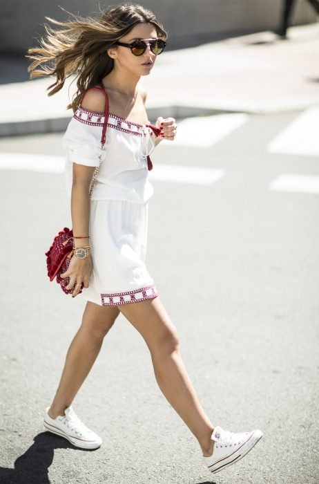 mujer con vestido blanco y tenis converse