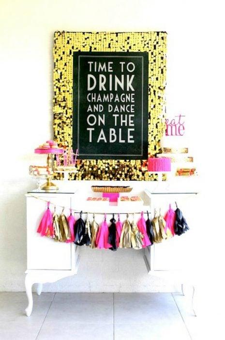 barra con comida para fiesta y decoracion rosa dorada y negro