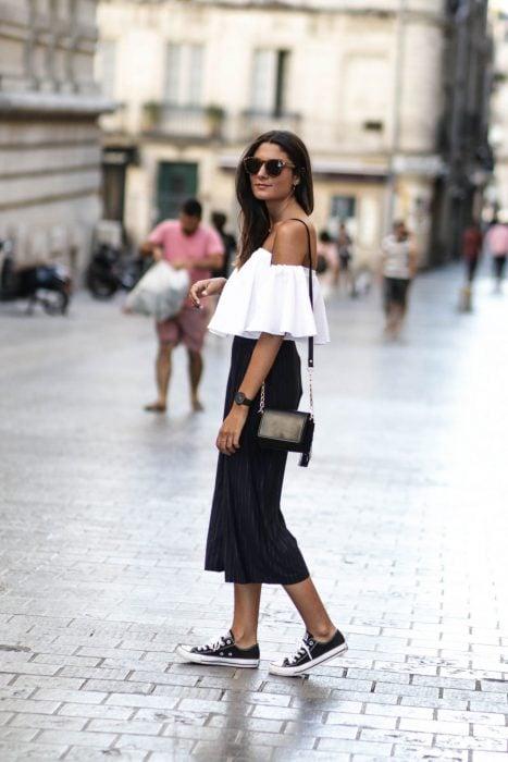 mujer con falda larga, blusa de hombros y tenis converse