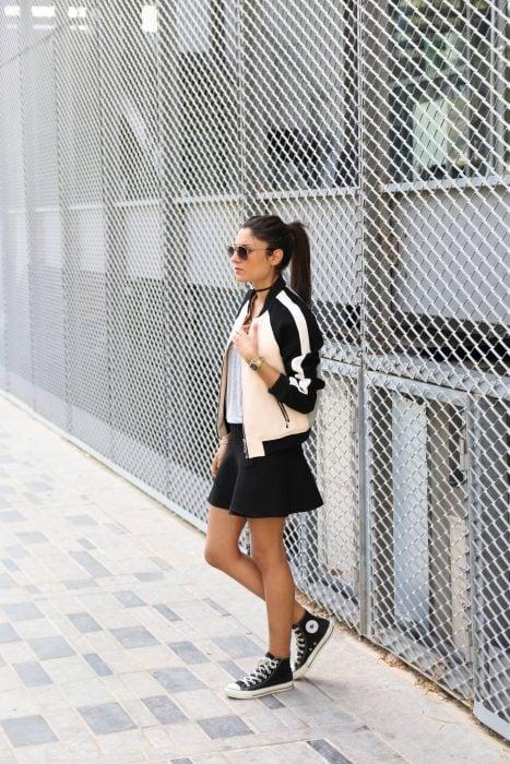 mujer con falda negra y chamarra de rayas