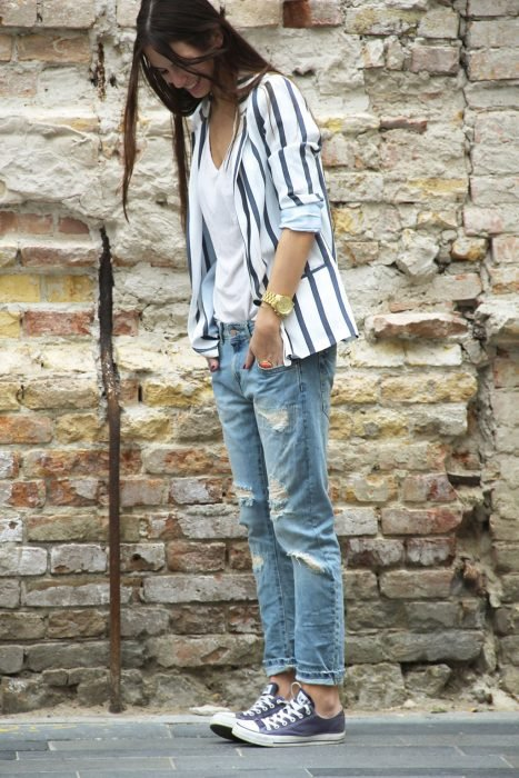 mujer con mezclilla con blazer de rayas y tenis converse
