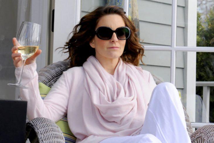 Actriz con una copa de vino blanco en la mano, mirando hacia el horizonte.