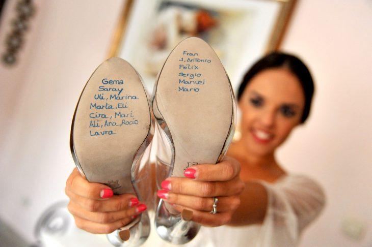 Novia mostrando sus zapatos con los nombres de las solteras.