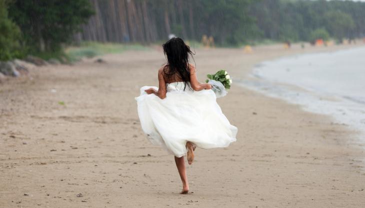 Mujer huyendo en vestido de novia.