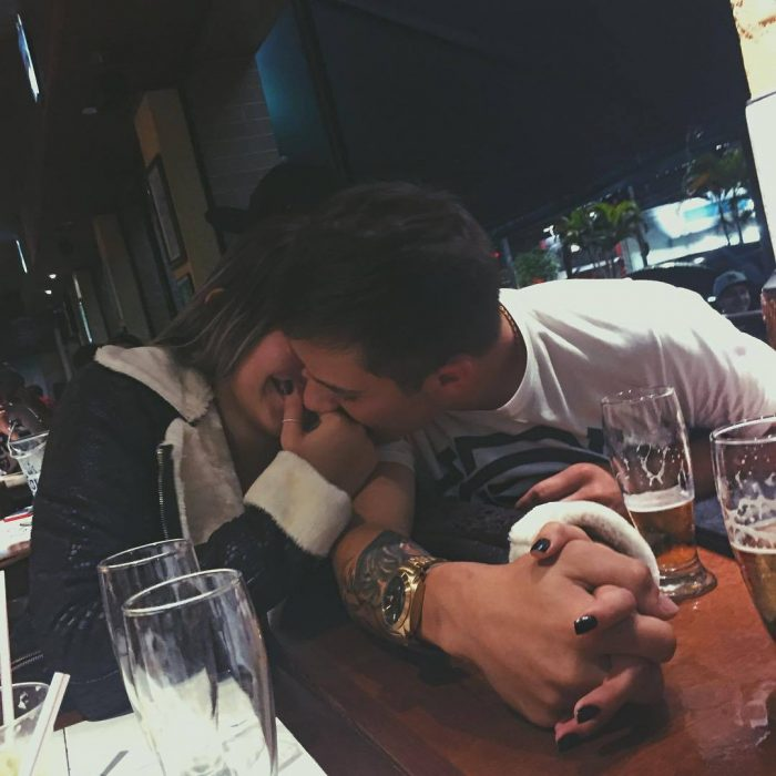 Pareja riendo mientras él le besa la mano.