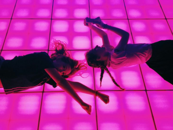 Amigas tiradas en medio de una pista fluorescente.