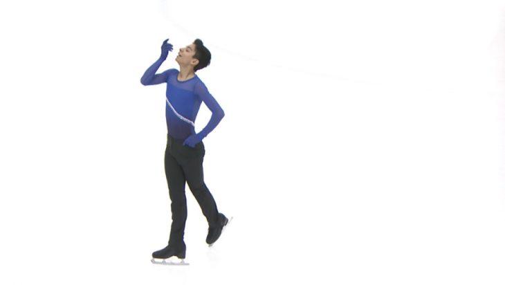 joven patinador vestido de azul sobre hielo