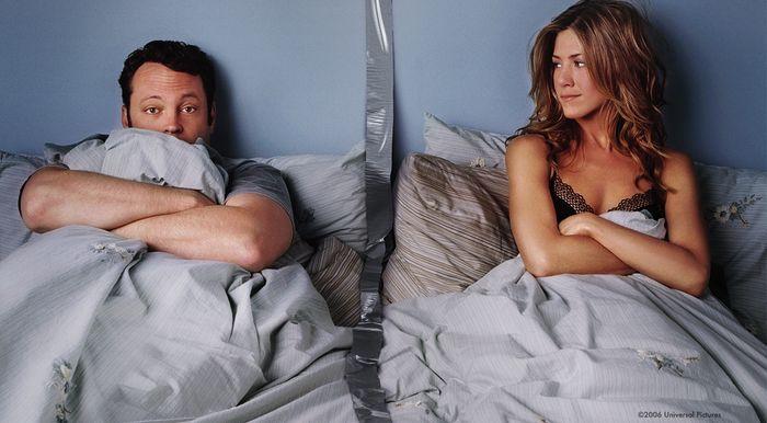 Actores juntos pero separados en una cama.