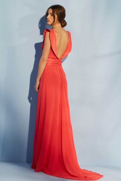 Woman modeling prom dress with backless.