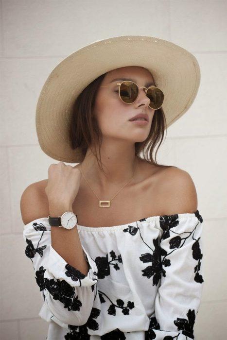Chica luciendo un escote barco, sombrero y lentes de sol.