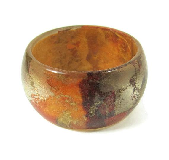 Brazalete de resina en tonos naranjas y marrones.