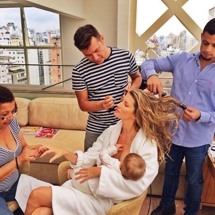 mujer rubia amamantando a bebe mientras la maquillan y arreglan