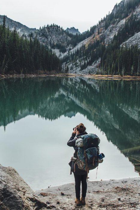 Chica tomando fotos a un lago mientras viaja