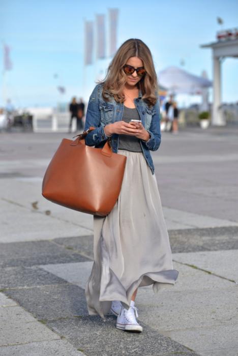 mujer rubia con falda gris y bolsa cafe con tenis converse