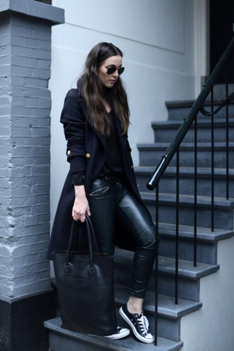 mujer vestida de negro con abrigo negro y tenis converse