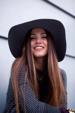 Joven con sombrero sonriendo.