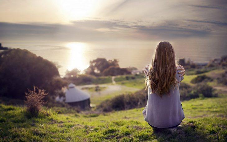 Chica sentada de espaldas mirando al horizonte.
