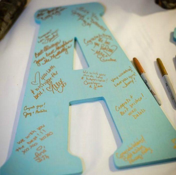 letra A de tabla con firmas y plumones sharpie