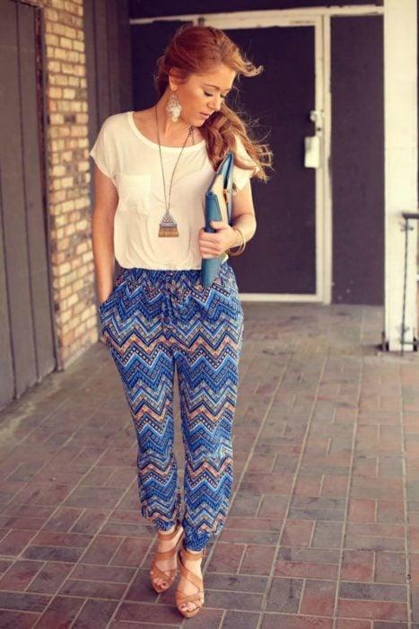 mujer con pantalon de estampado azul camisa blanca y cabello largo