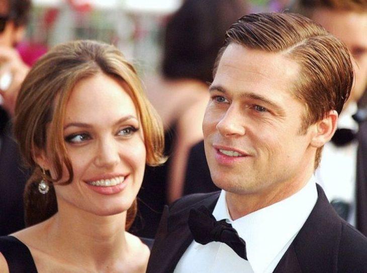 hombre rubio con traje y moño y mujer con aretes