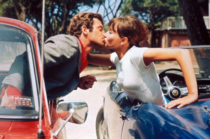 Pareja besándose de carro a carro.