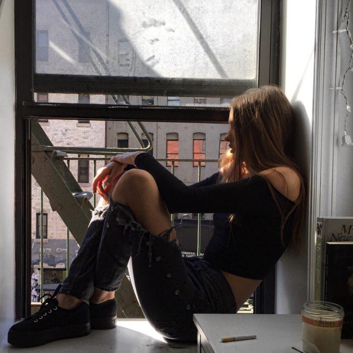Chica sentada bajo unas escaleras.