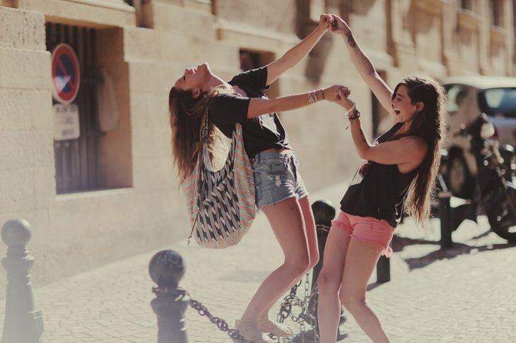 Muchachas jugando en una cadena de una avenida.