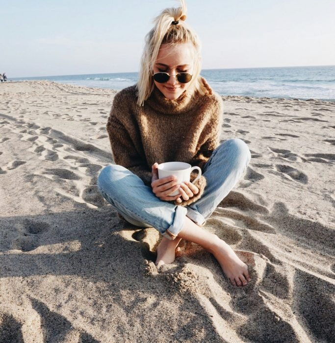 mujer rubia en la playa con lentes