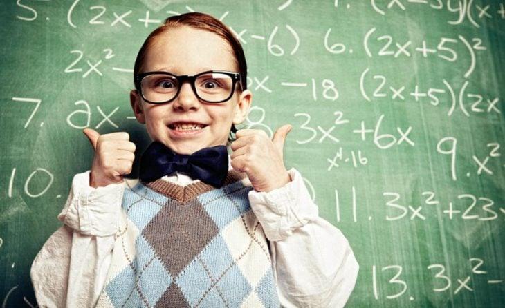 Niño con lentes apuntando al pizarrón.