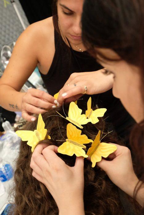 Equipo de maquillaje colocando la corona de mariposas.