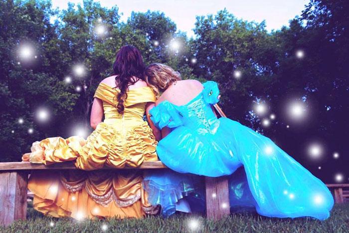 mujeres vestidas de princesas sentadas de espaldas