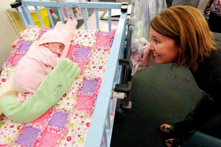 bebé en cuna y mujer sonriendo frente a el