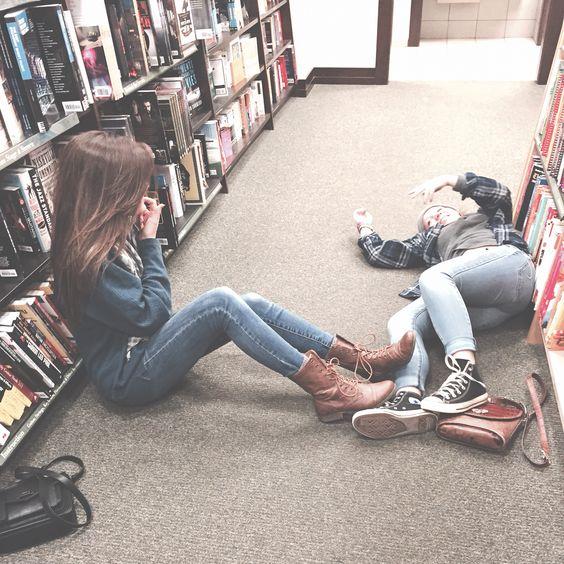 Chicas tiradas en medio de una biblioteca platicando.