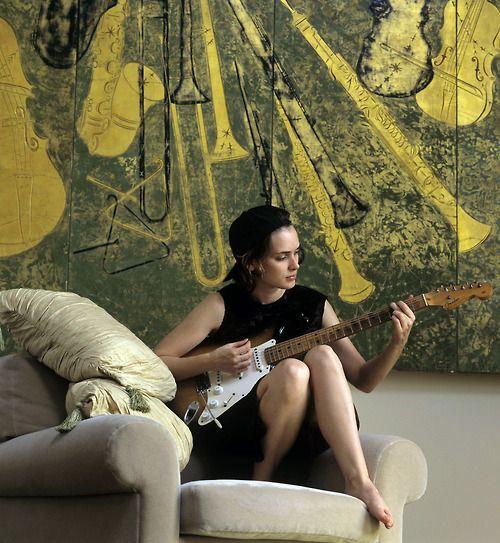 Winona Ryders tocando la guitarra.