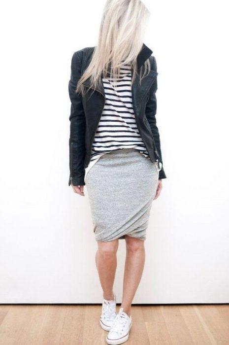 mujer con falda gris, chaqueta y tenis converse