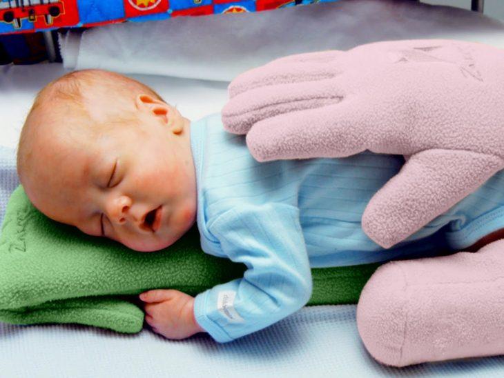 bebe abrazado de guantes de colores