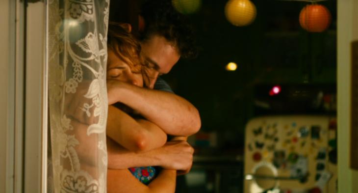 pareja abrazada en una ventana