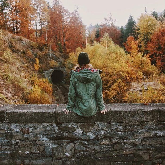 mujer sentada entre arboles en otoño